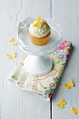 A cupcake decorated with a yellow butterfly on a white cake stand