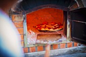 A freshly baked pizza in a wood-fired oven