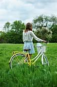Mädchen mit Fahrrad auf grüner Wiese