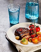 Slice beef steak with pink pepper and steamed cherry tomatoes