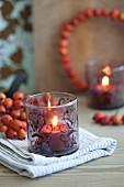 Nostalgisch bemaltes Windlicht mit brennender Kerze; dahinter ein Hagebuttensträusschen und ein Hagebuttenkranz