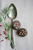 A silver spoon and pralines decorated with flowers