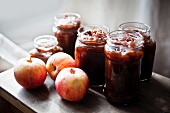 Jars of homemade apple chutney and fresh apples