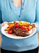 A woman holding a plate of steak, tomatoes and sweet potato wedges
