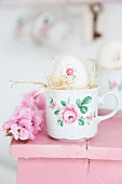 Easter egg decorated with napkin decoupage and straw in floral cup on pink footstool