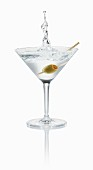 A Vodka Martini splashing out of the glass