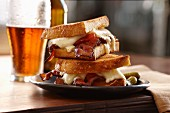 A toasted bacon and cheese sandwich with beer