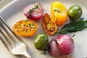 Roasted onions, yellow tomatoes, capers and sage (close-up)
