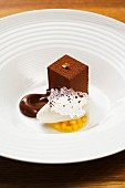 A chocolate cream cube and ice cream on mango jelly