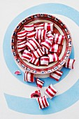 Red-and-white striped peppermint bonbons in a ceramic bowl