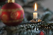 A Christmas decoration with s candle and a bauble