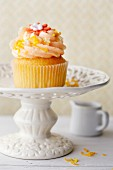 An orange and ginger cupcake on a cake stand with orange zest