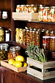 Various jars of preserves, fresh lemons and green asparagus