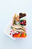 A lunch box with sandwiches, berries and peper