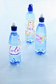 Three bottles of water with name tags