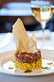 Tuna tartar on a bed of saffron couscous with green olives crispy poppadoms