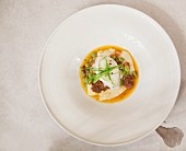 A poached organic egg served on celeriac puree with sausage and Edamame beans
