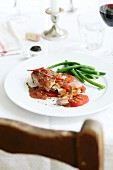 Pork steak on tomatoes with herbs and gravy