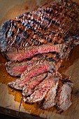 A flank steak, sliced, on a chopping board