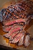 A flank steak, sliced, on a chopping board
