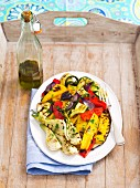 A plate of grilled vegetables and a bottle of olive oil on a wooden tray
