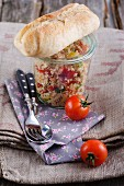 Couscous salad in a jar with a baguette and tomatoes