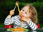 Girl eating spaghetti with tomato sauce