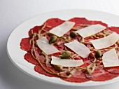 Salami carpaccio with cheese and capers