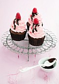 Chocolate cupcakes with raspberry cream and chocolate sauce