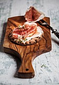 Crisp bread with Parma ham on a wooden board