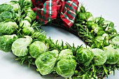 A Christmas wreath made with Brussels sprouts and rosemary with a checked ribbon
