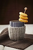 Doughnuts on a stick in a cup with a knitted holder