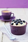 Rice pudding with blueberries and a cup of coffee in background