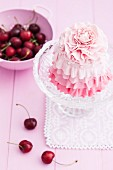 A cherry cake with pink icing