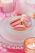 Pink macaroons in a glass bowl on a plate between candles