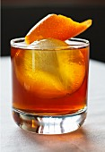 Whiskey with orange zest and an ice cube