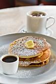 Gestapelte Pancakes mit Zucker, Butter und Kaffee