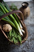 A basket of spring onions, beans and ginger next to a Japanese vase