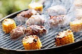 A smoking grill with corn cobs and meat