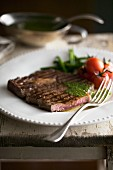 A grilled steak with herb sauce and vegetables