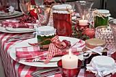 Weihnachtstisch mit rot-weiss kariertem Tischtuch, Stoffservietten, Marmeladengläsern und Kerzen