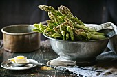 Green asparagus in a vintage bowl served with salt and butter