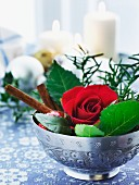 A Christmas table decoration with a rose and cinnamon sticks in a bowl