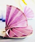 A decoratively folded purple napkin on a plate