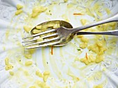 Remains of saffron risotto with cutlery on a plate