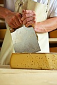 A dairyman cutting mountain cheese (Bregenzerwald, Vorarlberg, Austria)