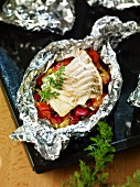 Pollack fillet on a bed of vegetables in aluminium foil