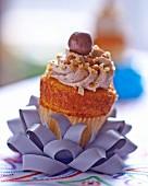 A nut cupcake on a decoratively folded ribbon