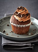 A chocolate cupcake with buttercream and pieces of choc