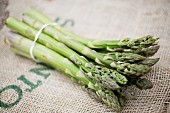 Green asparagus on a piece of jute